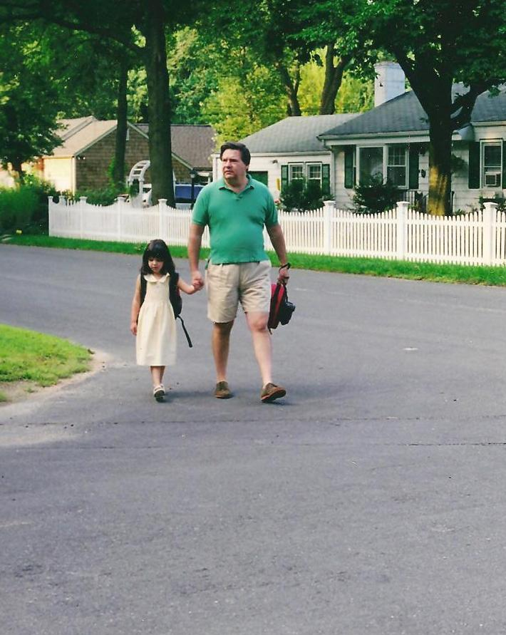 Catherine and Basil walk to the bus stop on the first day of kindergarten.